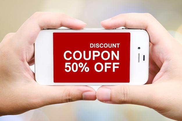 Mão digitando código de cupom de desconto na tela do smartphone para obter a promoção on-line de compras