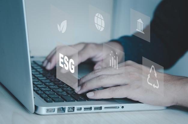 Mão digitando no símbolo do ícone do computador portátil de esg no conceito de tela vitrual. conceito de investimento esg (meio ambiente, social, governança) com foco no meio ambiente, na sociedade e na boa governança.