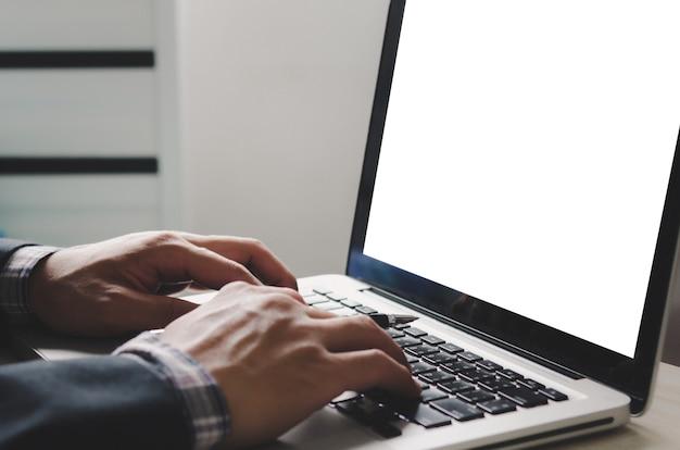 Mão digitando no teclado do laptop e simulando a tela do computador em branco. espaço em branco na tela para mídia de publicidade