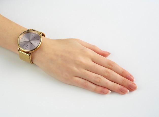 Mão direita da mulher com relógio de ouro