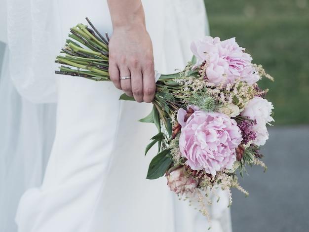 Mão direita de uma noiva segurando os buquês de flores sobre o vestido