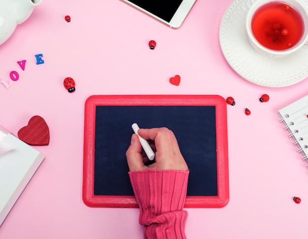 Mão direita feminina em um suéter rosa com um pedaço de giz branco