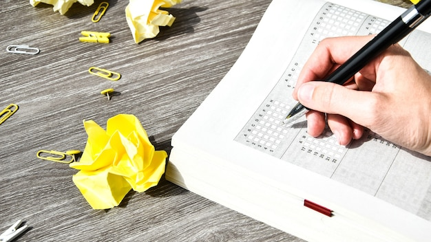 Mão do aluno com lápis para o exame