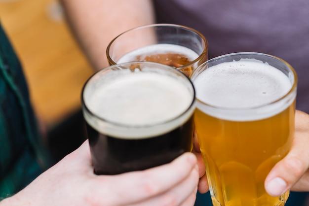 Mão do amigo brindando copo de bebidas alcoólicas