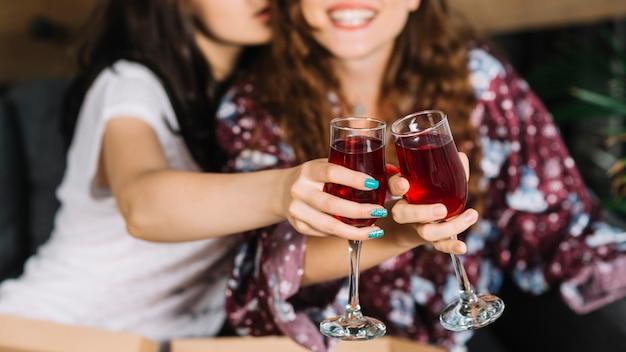 Mão do amigo feminino brindando óculos