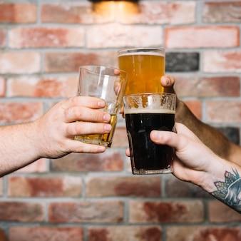 Mão do amigo masculino brindando copos de bebidas alcoólicas contra a parede de tijolos