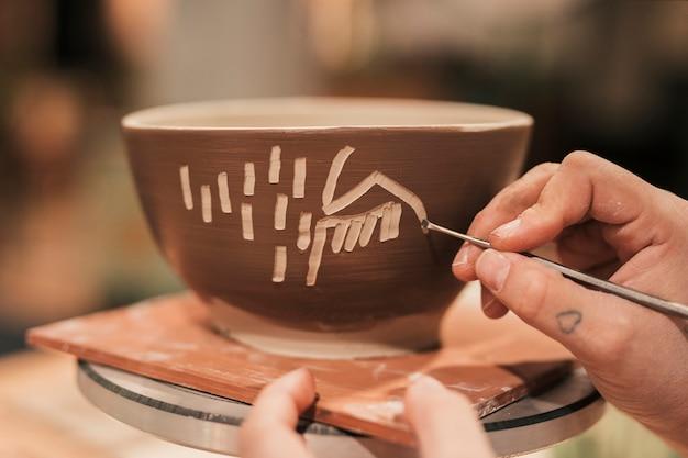 Mão do artesão feminino decorando a tigela com ferramenta