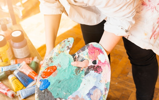 Mão do artista feminina segurando paleta de pintura desarrumado na oficina