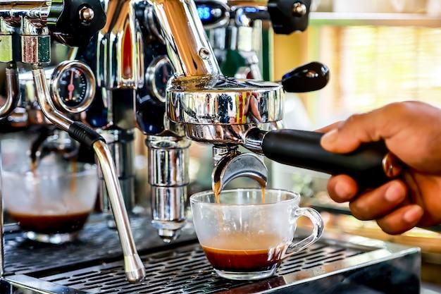 Mão do barista que faz o café do café com a máquina de café na cafetaria.