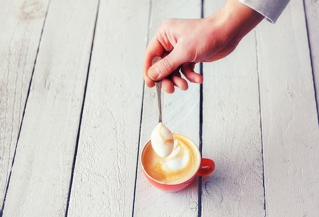 Mão do barista segurando uma colher com um delicioso creme de café com leite com padrão em uma xícara de cerâmica vermelha na mesa de madeira branca.