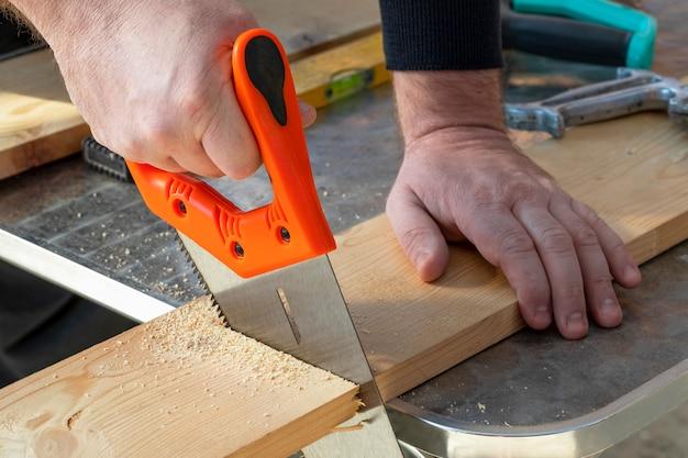 Mão do carpinteiro com as placas de madeira do corte do handsaw.