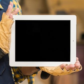 Mão do carpinteiro masculino com luvas de proteção, mostrando o tablet digital de tela em branco
