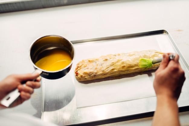Mão do chef masculino lubrifica strudel de maçã com ovo e manteiga. cozinhar sobremesas doces caseiras, processo de preparação