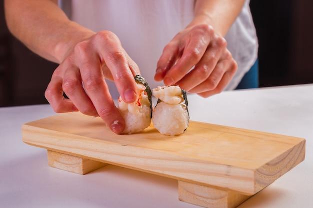 Mão do chef organizando sushi roll na placa de madeira.