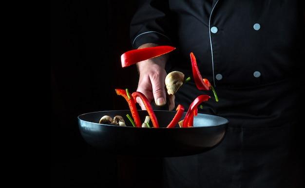 Mão do chef profissional jogando pedaços de vegetais e cogumelos na frigideira