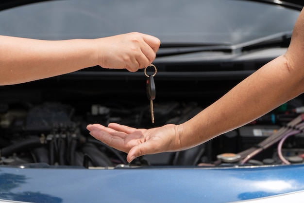 Mão do cliente dando a chave do carro para reparador de motor de carro
