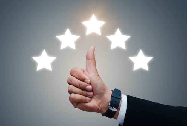 Mão do cliente mostra o polegar com avaliação de cinco estrelas.