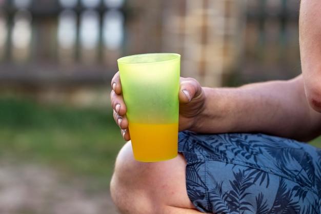 Mão do close up com copos de plástico. foco seletivo nas mãos /
