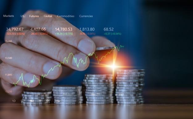 Mão do close up contando a pilha de moedas na mesa no conceito de negócios, investimento, comércio, bolsa de valores, negociando comerciante on-line com gráfico digital