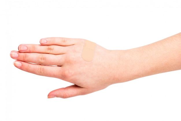 Mão do close-up da jovem mulher com uma atadura adesiva.