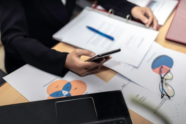 Mão do close-up das mulheres de negócio com escrita de papel no gráfico.