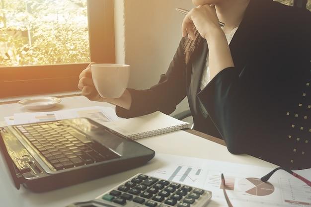 Mão do close-up das mulheres de negócio que guarda o café com escrita de papel no gráfico.