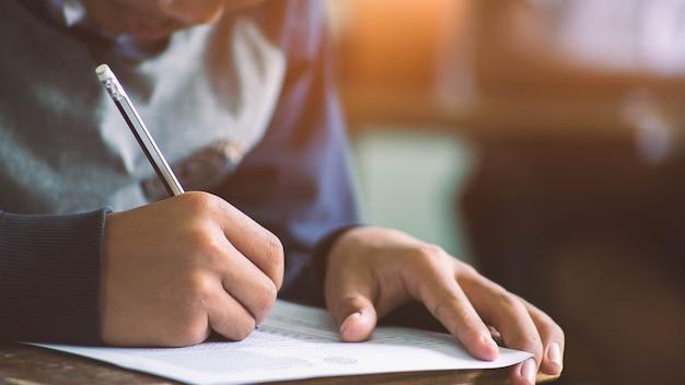 Mão do close-up de escrever o exame com os estudantes no curso.