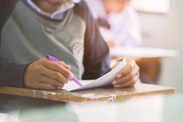 Mão do close-up de escrever o exame com os estudantes uniformes no curso.