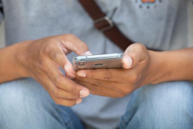 Mão do close up do adolescente asiático do homem usando o telefone esperto com espaço.