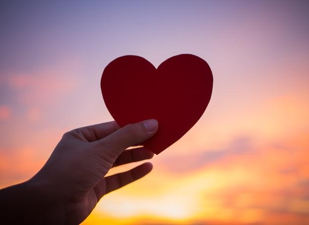 Mão do close up que guarda o coração vermelho durante o fundo do por do sol.