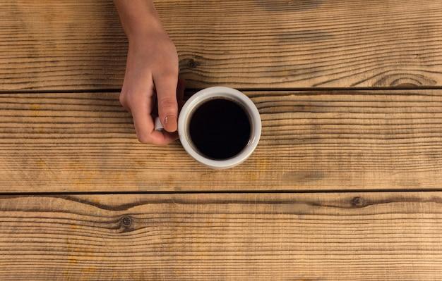 Mão do close up que guarda uma caneca de café em uma tabela de madeira.