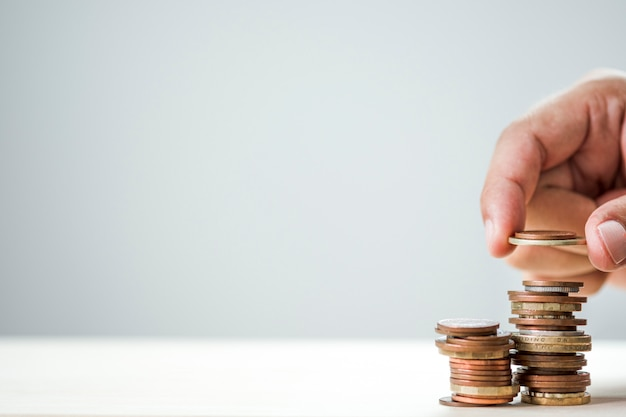 Mão do close up que põe as moedas crescentes que empilham com fundo branco.