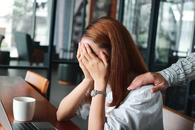 Mão do colega reconfortante triste mulher asiática