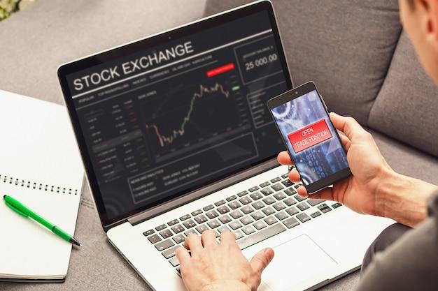 Mão do comerciante, segurando a tela de toque do telefone móvel mostrando compra e venda no mercado de ações
