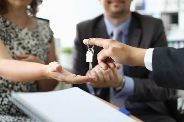 Mão do corretor de imóveis segura casa chave contra escritório