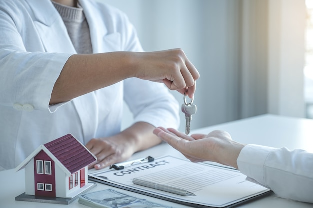 Mão do corretor de imóveis, segure as chaves e explique o contrato comercial, aluguel, compra, hipoteca, empréstimo ou seguro residencial.