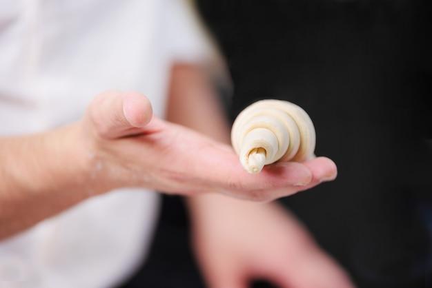 Mão do cozinheiro chefe de pastelaria que mostra um croissant cru fresco.