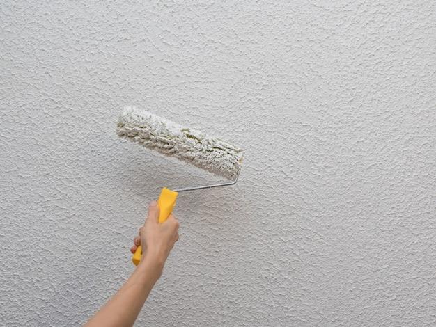 Mão do decorador que pinta a parede branca com rolo.