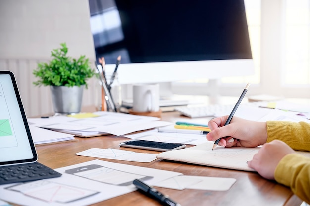 Mão do desenhista fêmea que trabalha com seu projeto novo no escritório moderno.