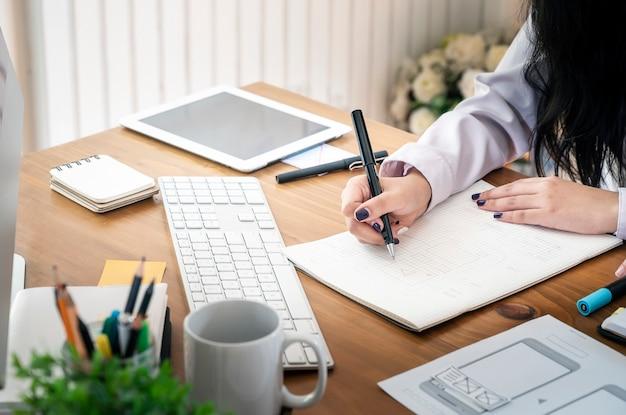 Mão do desenhista fêmea que trabalha com seu projeto novo no escritório.
