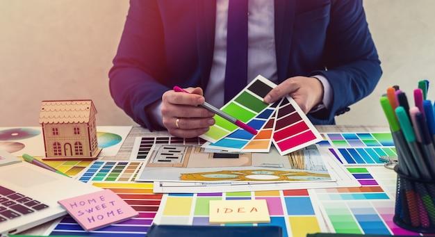 Mão do designer de interiores trabalhando com esboço de ilustração, esquema de cores do material, caderno e material. conceito de renovação, reparo ou decoração de uma casa