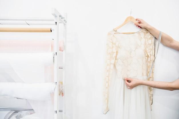 Mão do designer de moda, tendo a medição do vestido novo