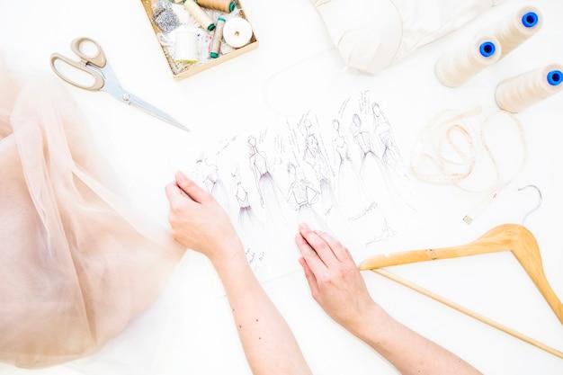 Mão do designer feminino segurando o esboço de moda sobre a mesa