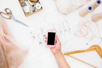 Mão do designer feminino segurando o telefone móvel sobre o esboço de moda