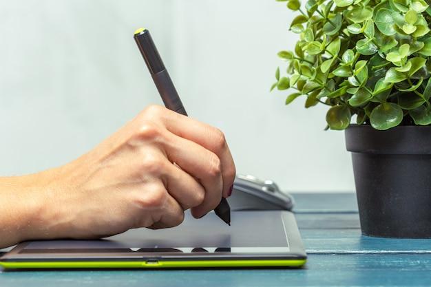 Mão do designer gráfico, trabalhando com estilete e tablet