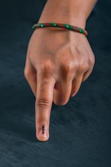 Mão do eleitor indiano com sinal de voto após voto de seleção nas eleições