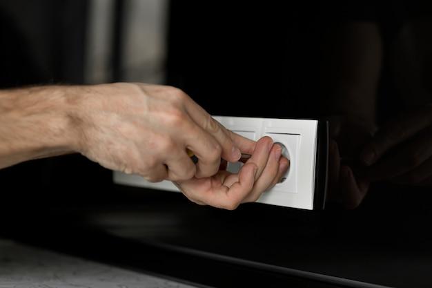 Mão do eletricista com uma chave de fenda desmontar uma tomada elétrica branca em uma parede de vidro preto.