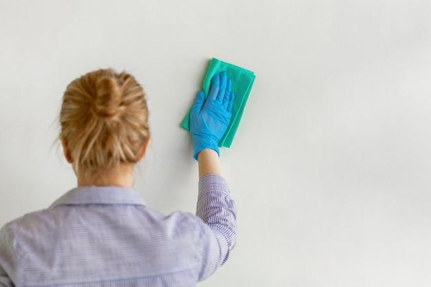 Mão do empregado na luva protetora de borracha azul que limpa a parede da poeira com o pano seco.