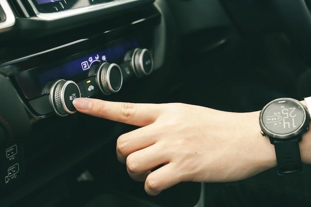 Mão do empresário abrir o volume do condicionador de ar no botão do carro. carro confortável ou sistema no conceito de carro.