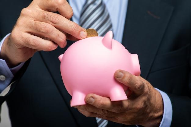 Mão do empresário colocando dinheiro em um cofrinho
